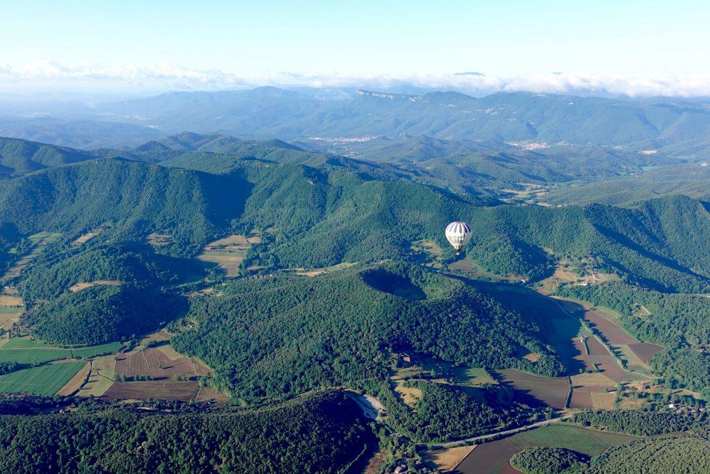 Blick auf die grüne Landschaft, einen bewachsenen Kraterkegel der Garroxta von oben, ein Heißluftballon steigt gerade auf