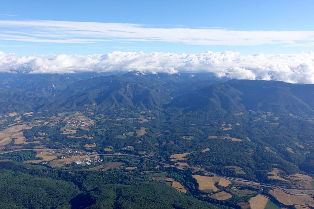 Landschaft der Garroxta von oben (im Heißluftballon): eine dicke Wolkendecke liegt über den grünen Hügel der Garroxta; dazwischen sind gelbe Felder