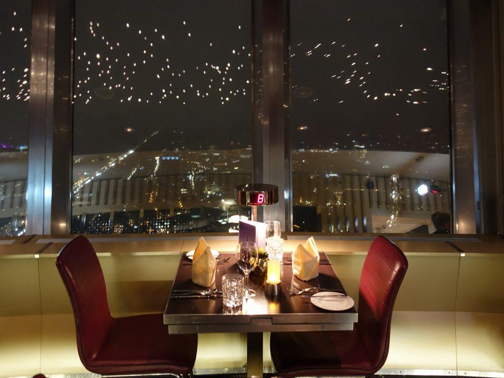 Ein 2er Tisch mit roten Stühlen am Fenster des Fernsehturms im Restaurant Sphere in Berlin