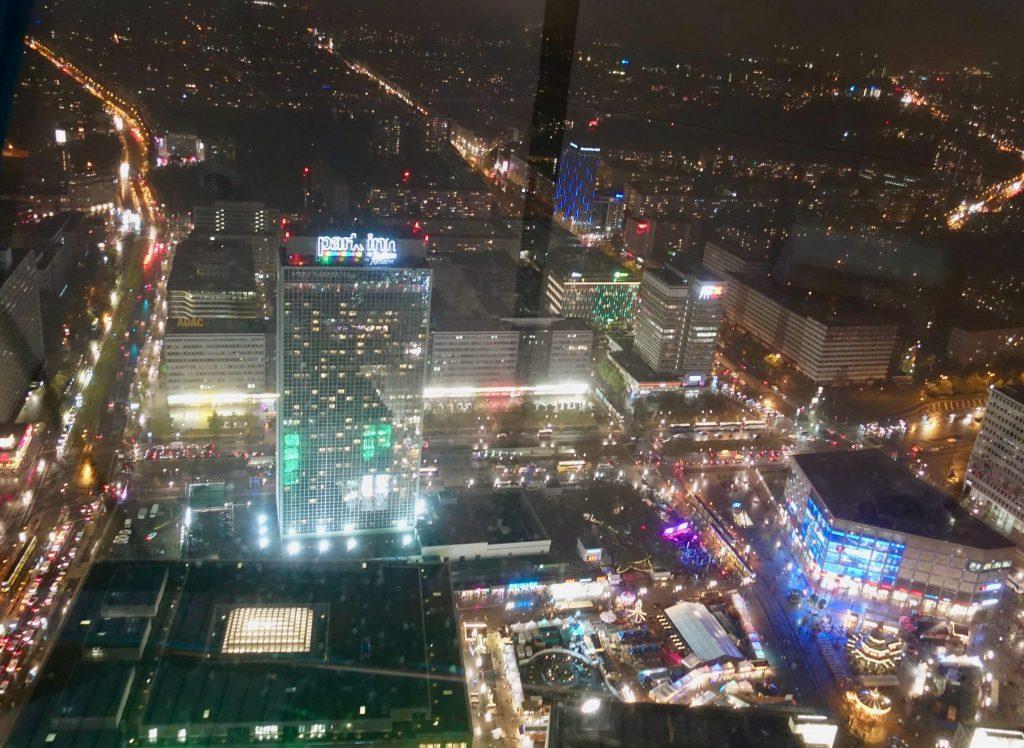 Aussicht bei Nacht vom Berliner Fernsehturm auf die hell erleuchteten Gebäude und Straße der Stadt