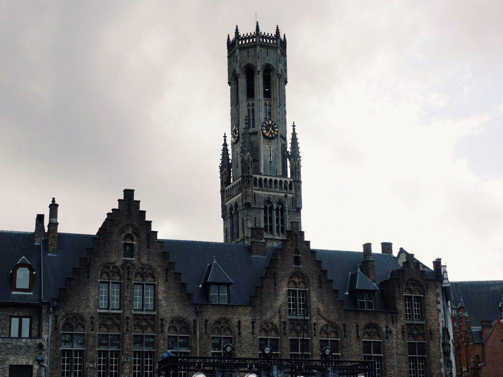Der Belfried Turm ragt über mittelalterliche Häuser auf