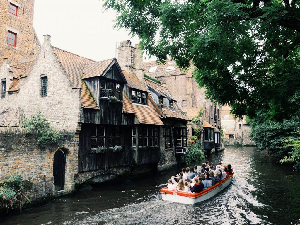 Am engen Kanal fährt ein Motorboot an einem alten Haus vorbei