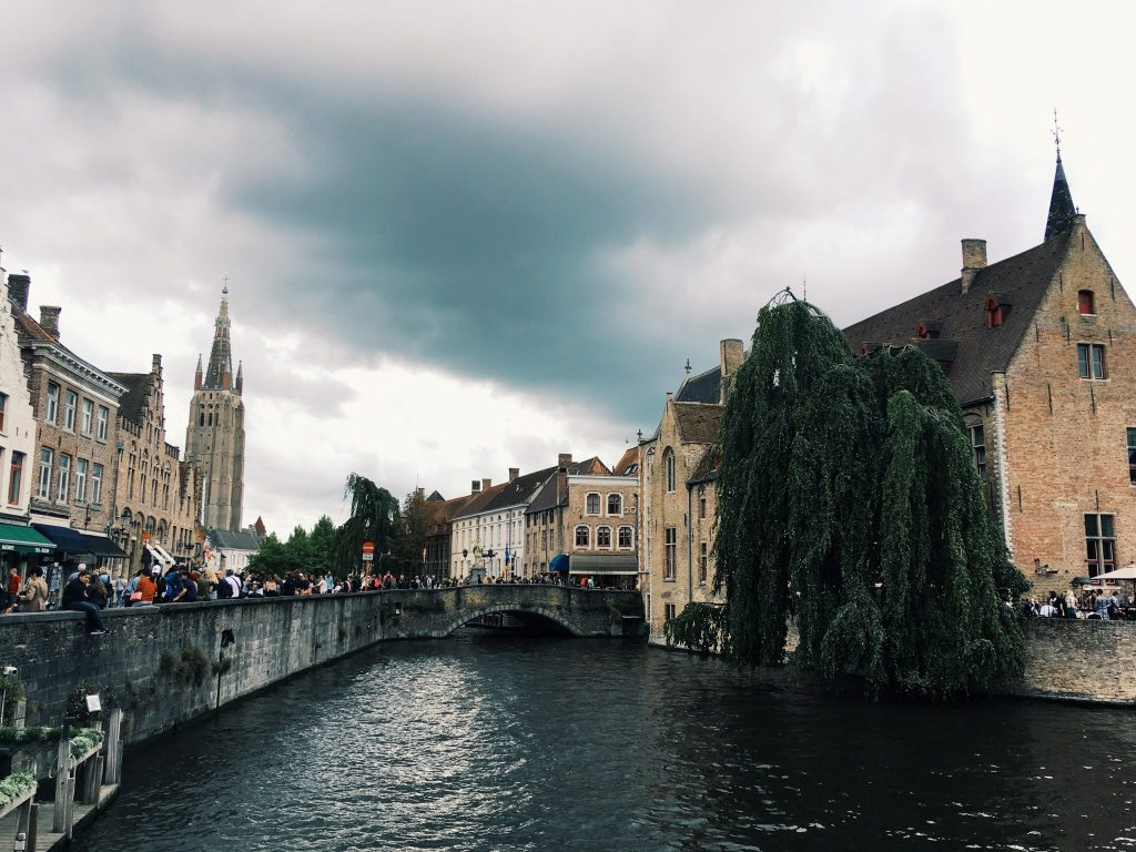 Ein Kanal gesäumt von einer Mauer mit vielen Menschen dahinter und Häusern