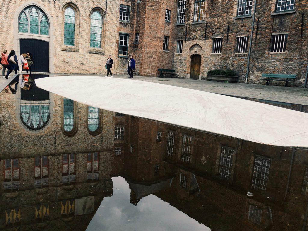 Ein Wasserbecken mit Spiegelung der Gebäude und ein paar Menschen