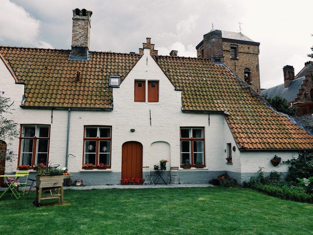 Ein weißes Haus mit roter Tür und Fensterrahmen
