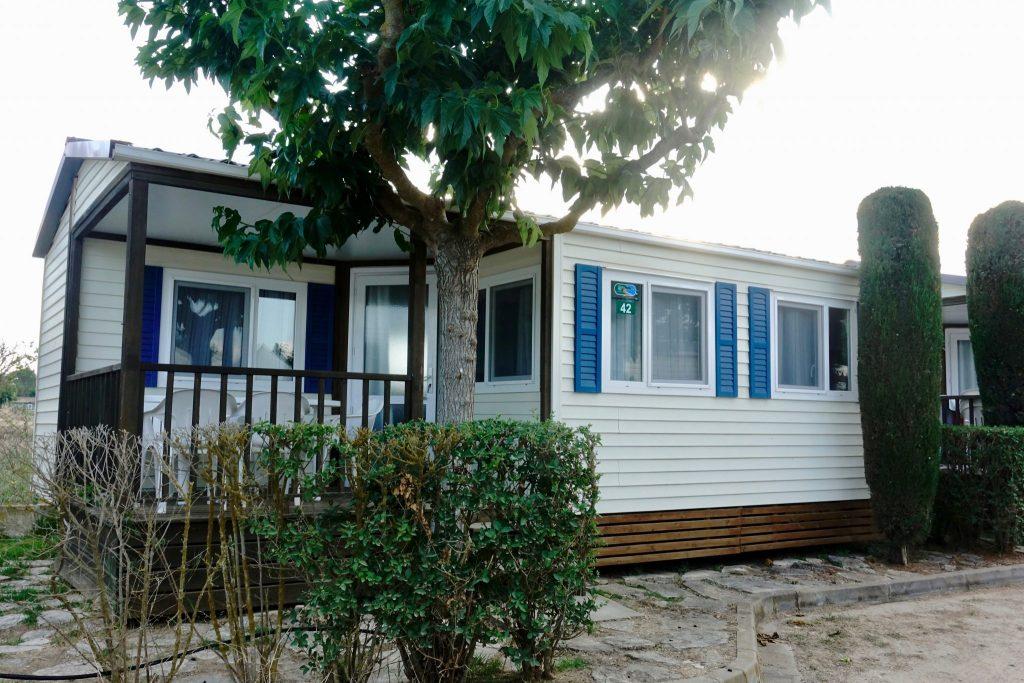 Weißer Bungalow mit blauen Fenstern und überdachter Terrasse im Camping Castell Mar