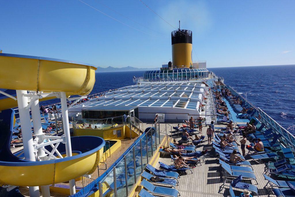 Eine gelbe Rutsche ist links im Bild zu sehen. Das Deck des Kreuzfahrtschiffes ist voll von Liegestühlen