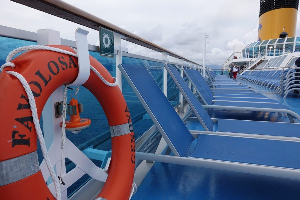 Ein oranger Rettungsring ist links im Bild. Danach sind viele blaue, leere Liegenstühle zu sehen