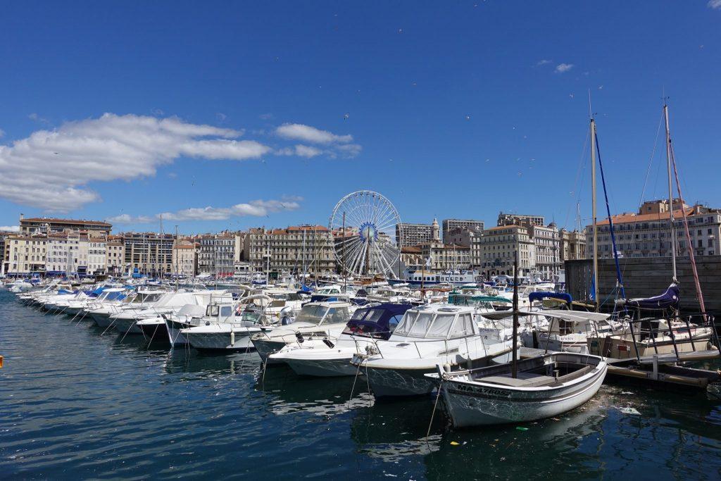 Unzählige Boote liegen im alten Hafen von Mareille, dahinter sind Häuser und ein Riesenrad zu sehen