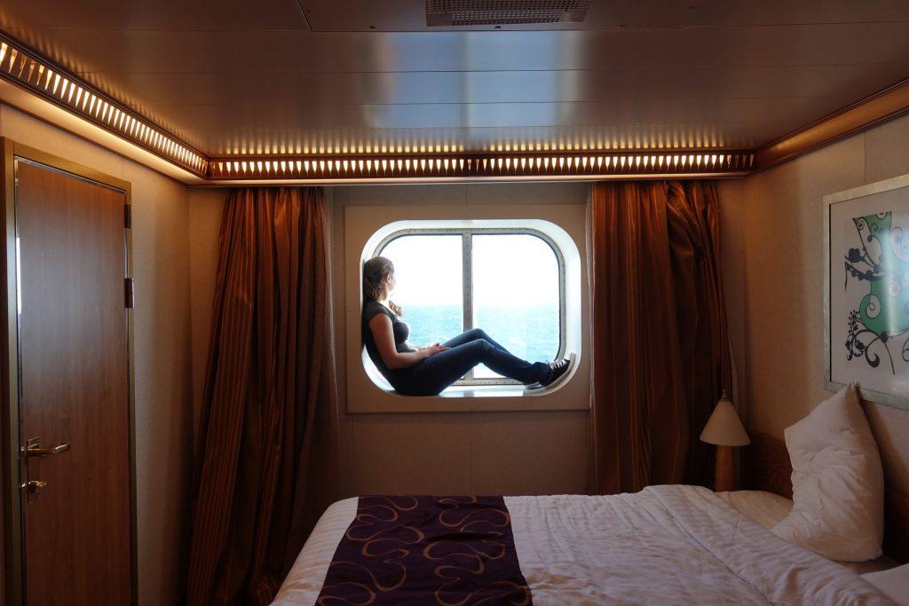 Ich sitze im Fenster der Außenkabine und schaue aufs Meer. Davor ist das Bett zu sehen.