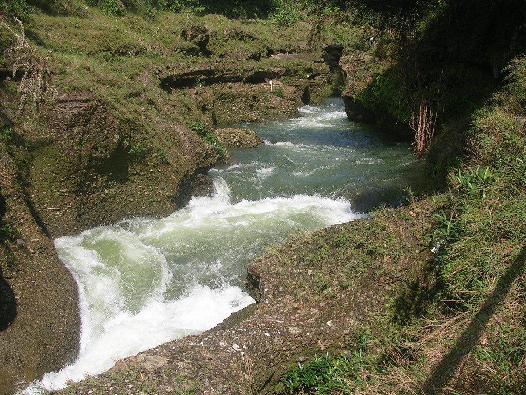 Der Pedi Khola kurz bevor er beim Devi´s Falls in die Tiefe stürzt: zwischen zwei braunen Uferseiten ist der grüne Fluss zu sehen mit vorne weiß schäumender Gischt