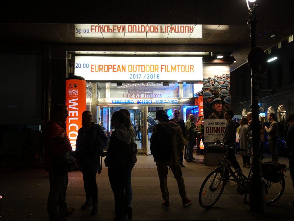 """Der beleuchtete Eingang mit der Beschriftung """"European Outdoor Filmtour"""" beim Gartenbaukino im Wien bei Dunkelheit"""