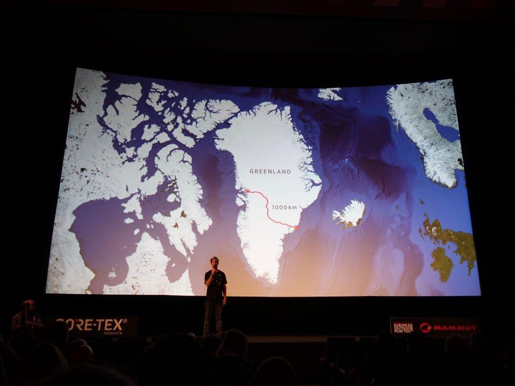 Grönland mit der eingezeichneten Wegstrecke wird auf der Leinwand gezeigt, davor der Moderator