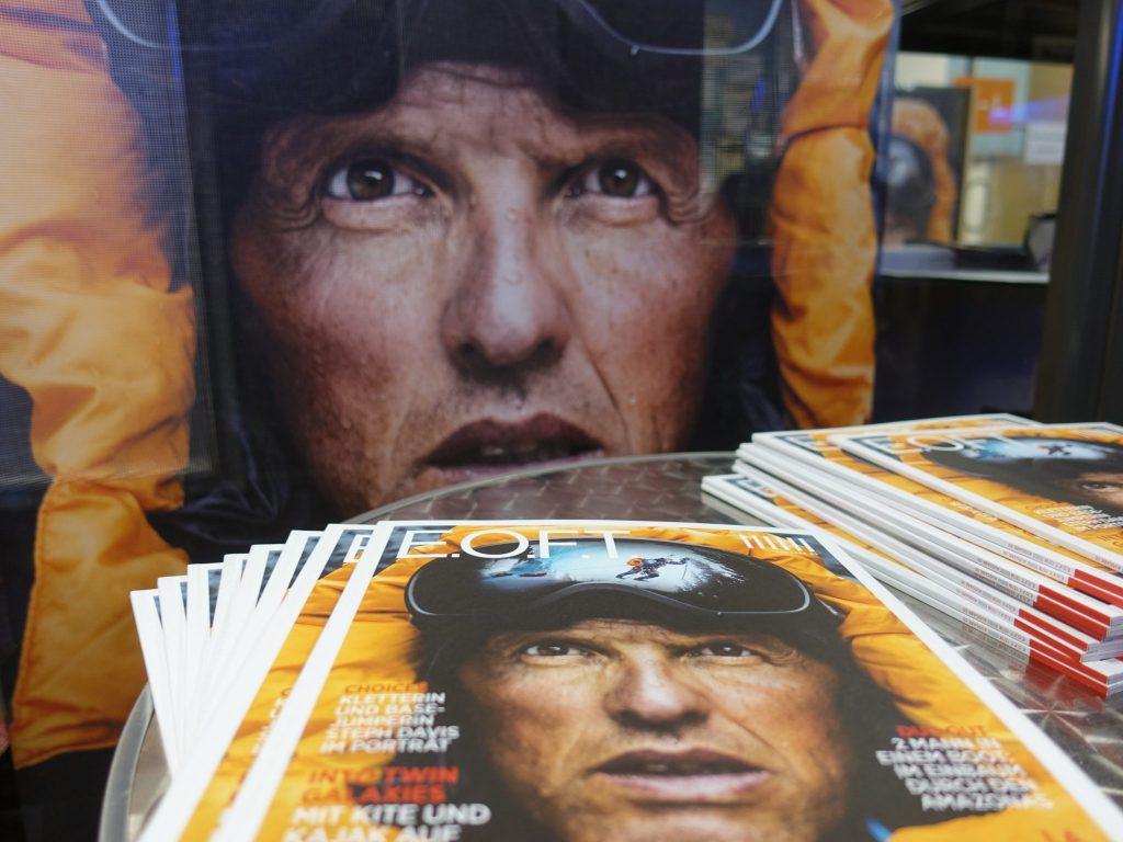 Die Zeitschriften im Vordergrund und das Plakat der EOFT 2017 im Hintergrund (auf beiden abgebildet ist das Gesicht des Extrembergsteigers Simone Moro)
