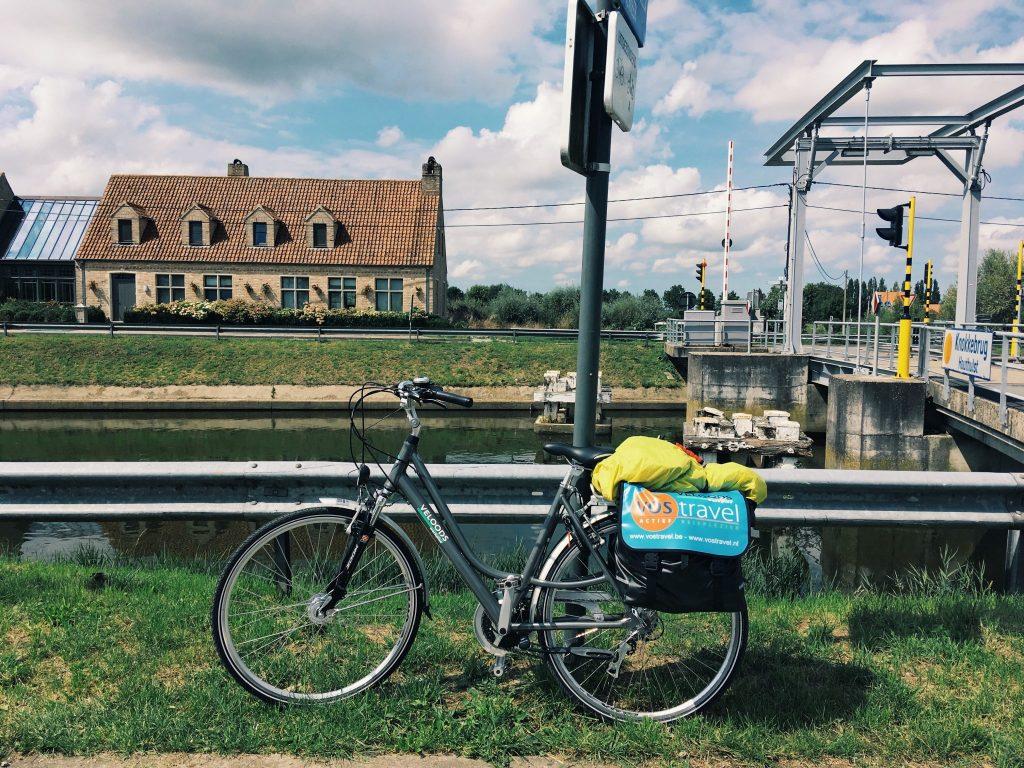 Ein Rad angelehnt an einen Wegweise mit Haus und Brücke im Hintergrund