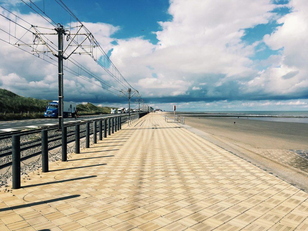 Ein breiter Weg neben einer Bahntrasse am Meer
