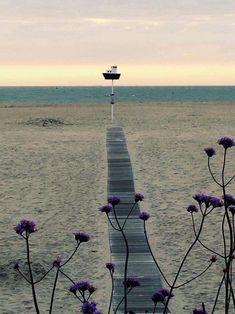 Ein Steg führt durch den Sand zu einem Schild mit Schiff, dahinter das Meer