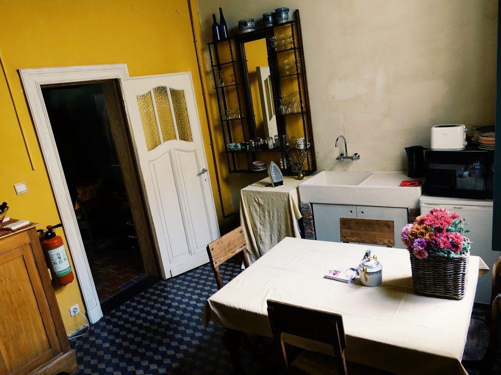 Detailreich eingerichtetes Zimmer mit Tisch, Waschbecken, Bügeleisen etc.