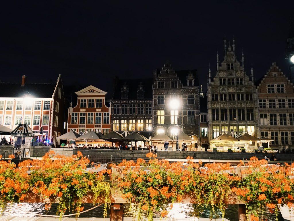 Rote Blumen dahinter die Hausreihe der Graslei in Gent