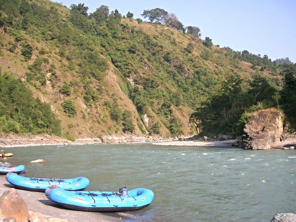 Raften am Kali Gandaki: blaue Boote liegen am Flussufer