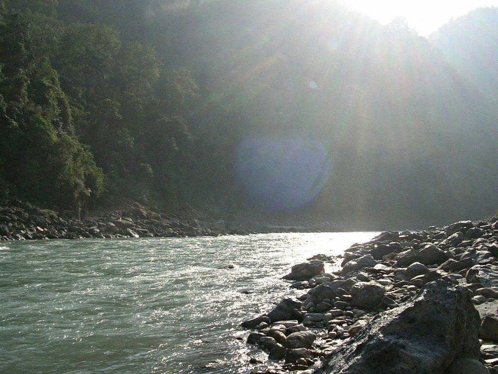 Die Sonne scheint auf den Fluss Kali Gandaki mit einem Ufer voller großer Steine