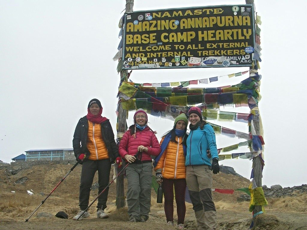 "Sun Maya, Palee, Uti und ich stehen vor dem Annapurna Base Camp Schild, auf dem steht: ""Amazing Annapurna Base Camp Heartly Welcome to all external and internatal trekkers"" auf 4200m; der Himmel ist ganz weiß vor Nebel"