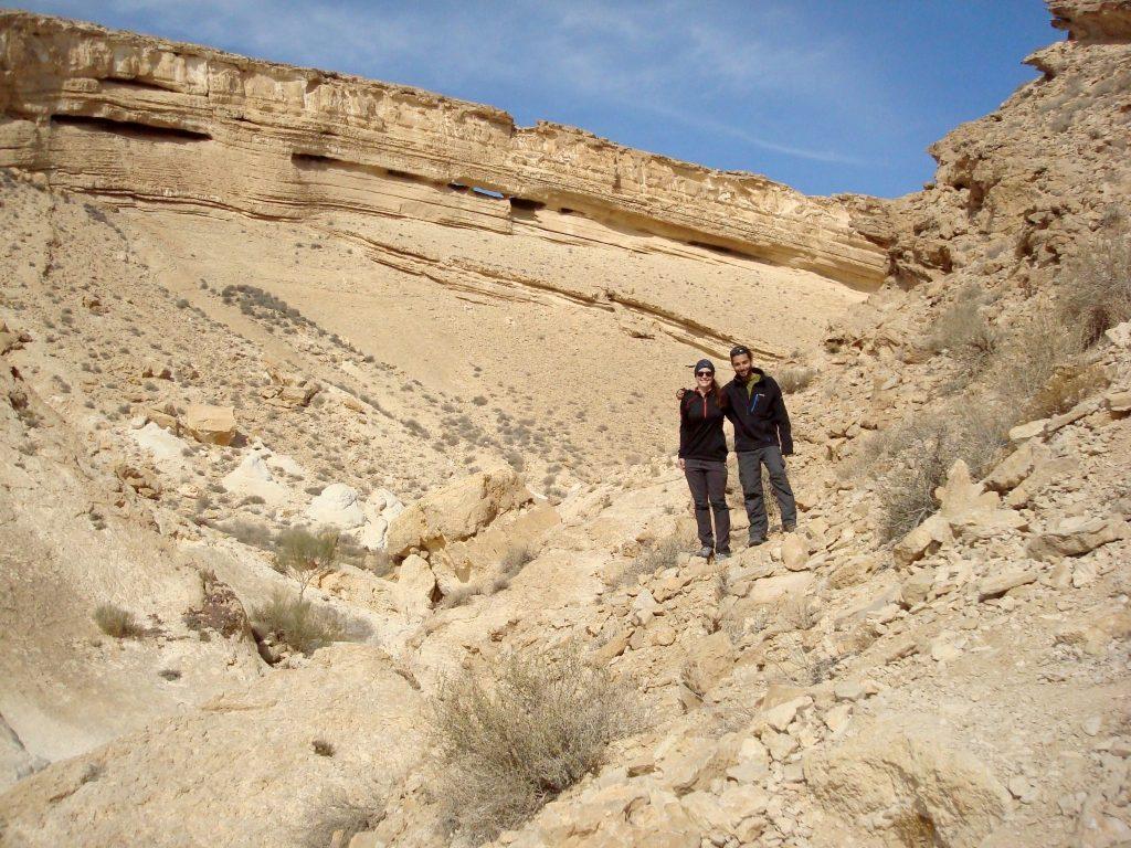 Zwei Menschen stehen vor einer riesigen Felswand