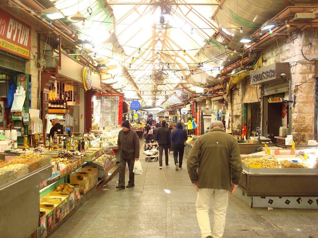 Durchgang in einem Markt, links und rechts die Stände, dazwischen ein paar Menschen, die durch den Markt hindurchschlendern