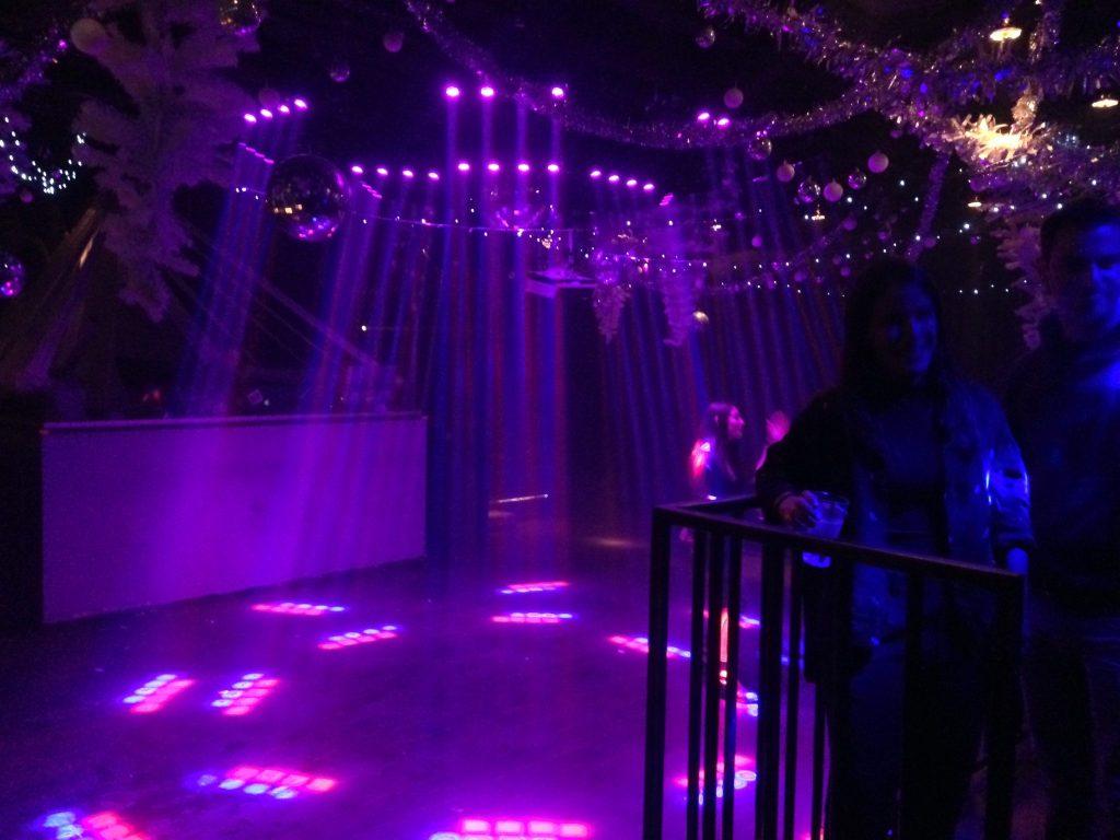 Eine violett beleuchtete Tanzfläche in einem Club