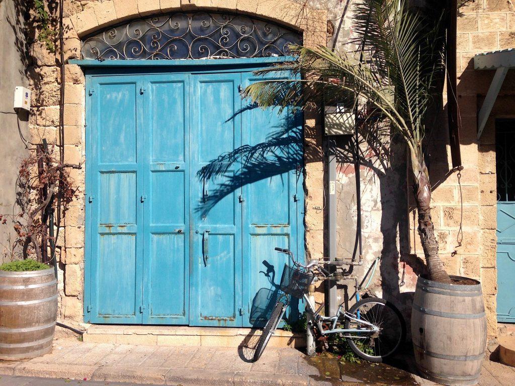 Eine hellblaue große Tür, rechts ein Fahrrad und eine Palme