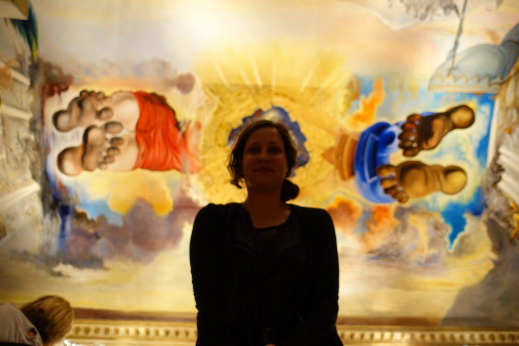 Ein Deckengemälde mit gelben Hintergrund im Theatermuseum Dali in Figueres; links (mit blauer Hose) und rechts (mit roter Hose) sind die Fusssohlen und Unterkörper zweier Menschen zu sehen, die etwas gemeinsam nach oben zu halten scheinen; ich bin in schwarz bekleidet in der Mitte des Bildes zu sehen