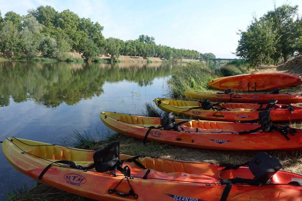 Die gelborangen Kayaks liegen am Ufer des Fluss Fluvià rechts im Bild; der Fluss und das gegenüberliegende mit Bäumen bewachsene Ufer ist im Hintergrund