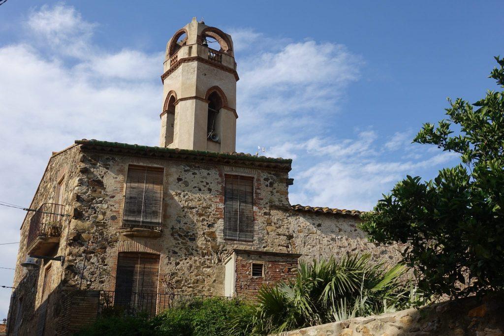 beiger Kirchturm mit roten Rändern in Mollet de Peralada, davor befindet sich ein altes Steinhaus mit verschlossenen Fensterläden