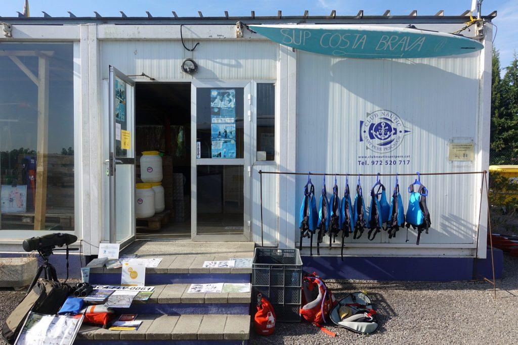 Containerhäuschen von Sk Kayak beim Club Nautic in Sant Pere Pescador mit Stufen; blauen Schwimmwesten hängen auf einer Stange