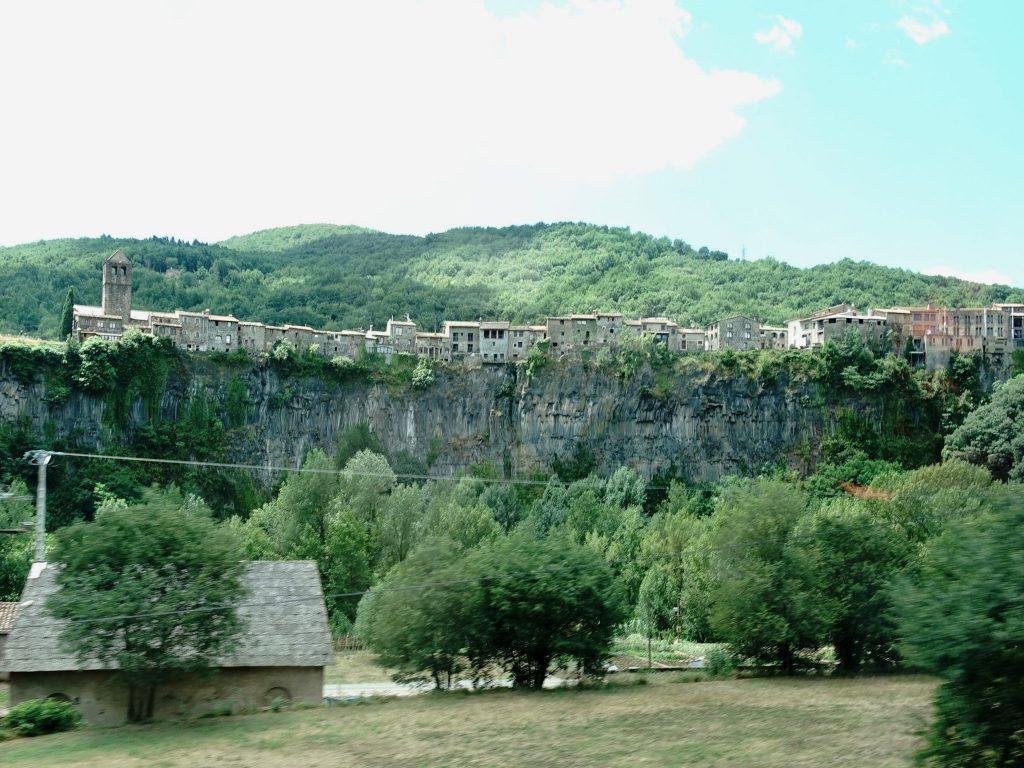 Die 700m hohe Klippe von Castellfollit de la Roca beim Vorbeifahren; im Vordergrund Bäume