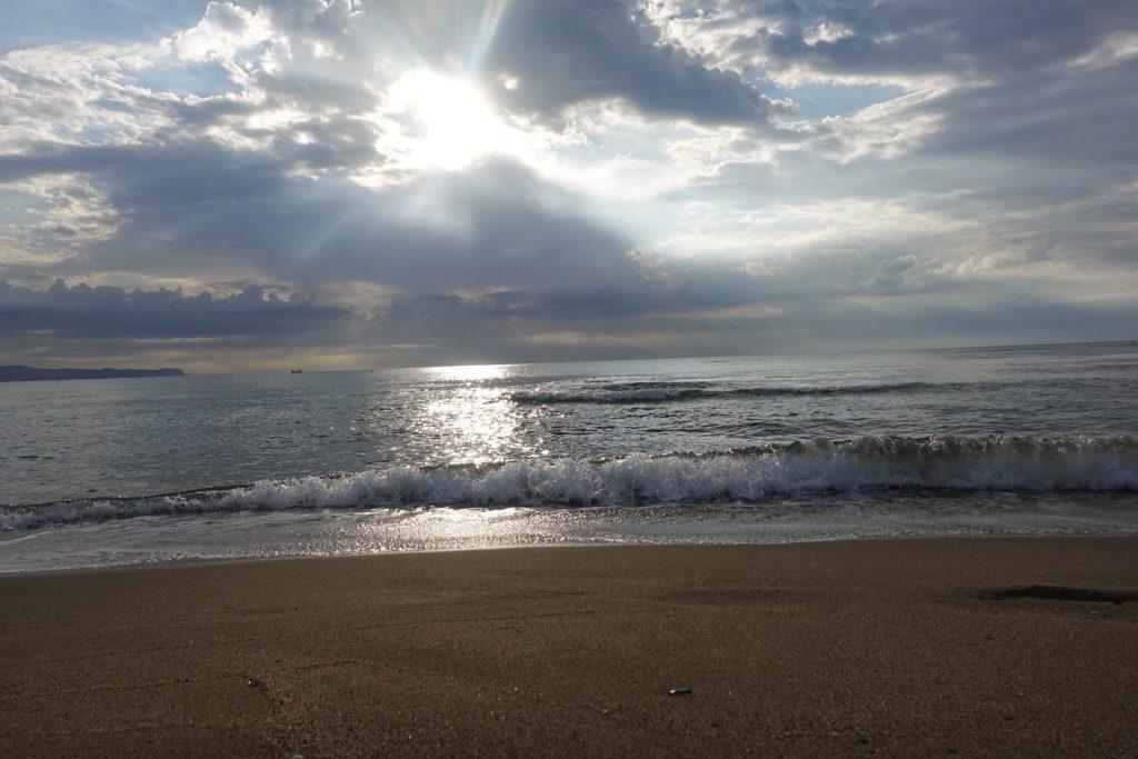 In der Bucht von Roses vor dem Campingpatz Las Dunas: die Sonne ist am untergehen und von Wolken verdeckt, das blaue Meer mit einer kleinen gebrochenen, weißen Welle und Strand