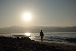 Theresa am Strand in der Bucht von Roses bei Sonnenaufgang