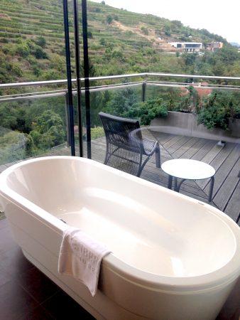 Freistehende Badewanne mit Ausblick auf die Weinberge im Steigenberger Krems