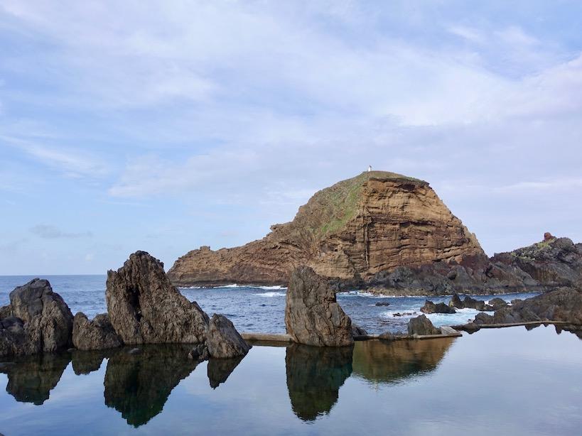 Wasserbecken mit Spiegelung der Felsen, ein Hügel und das Meer im Hintergrund