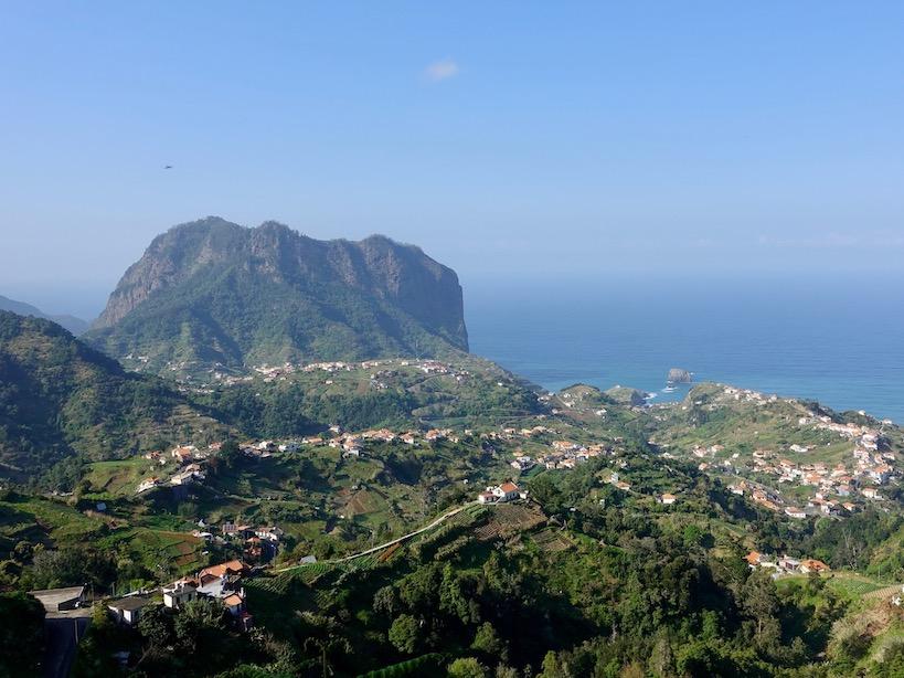 Hügelige, grüne Landschaft und ein markanter eckiger Berg auf der linken Seite, das Meer ist im Hintergrund
