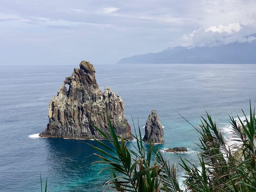 Ein spitzer, dreiecksförimiger Fels im ruhigen Meer