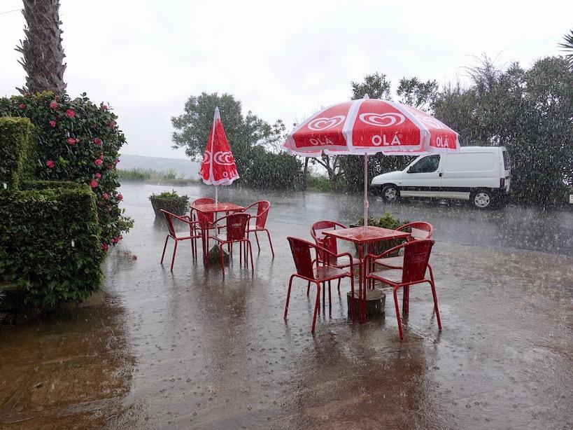 Rote Sitzmöbel mit Sonnenschirm im Regen
