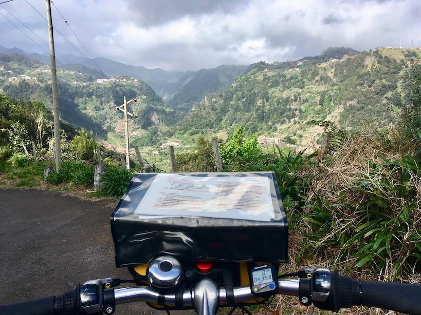 Lenker des Fahrrads mit Routenbeschreibung vor einer grünen hügeligen Landschaft, die Wolken sind grau