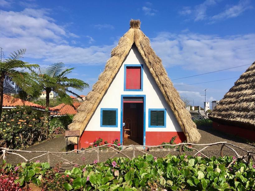 Strohbedecktes spitzes, weißes Haus mit blauen Umrandungen der Türen und Fenster und roten Bodenabschluss