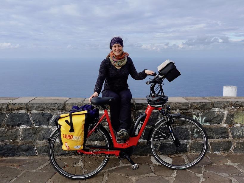 Rotes Rad mit gelber Satteltasche, Schwarz angezogene Person (ich) sitzt auf Steinmauer, dahinter das Meer