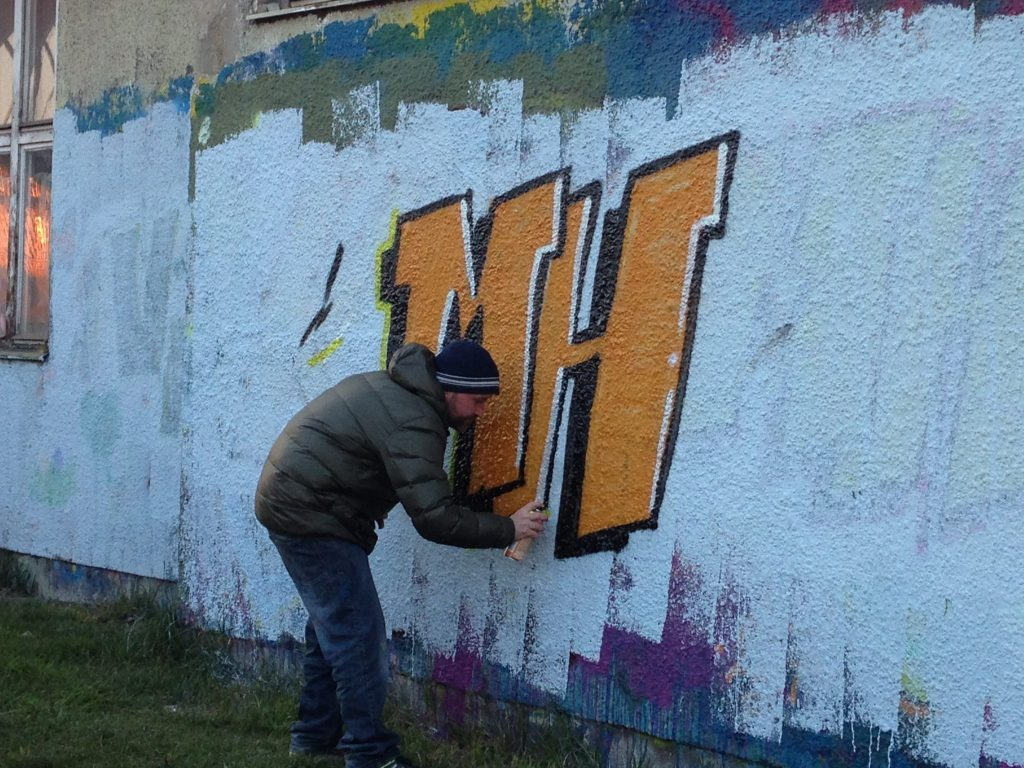 SHED alias beim Erklären der einzelen Schritte wie ein Graffiti entsteht. Dabei sprüht er die MH mit oranger Farbe an die weiße Wand.