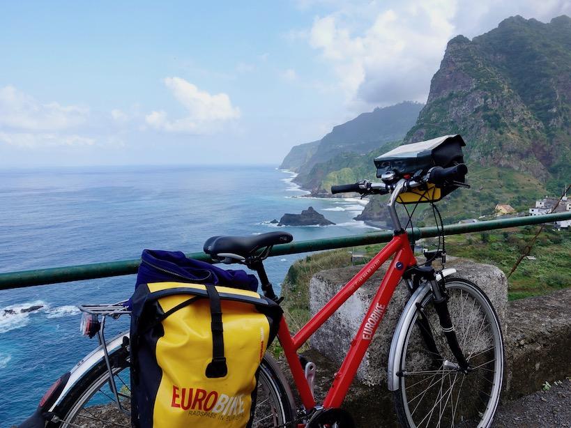 Ein rotes Rad mit gelber Seitentasche vor dem Meer und der Steilküste
