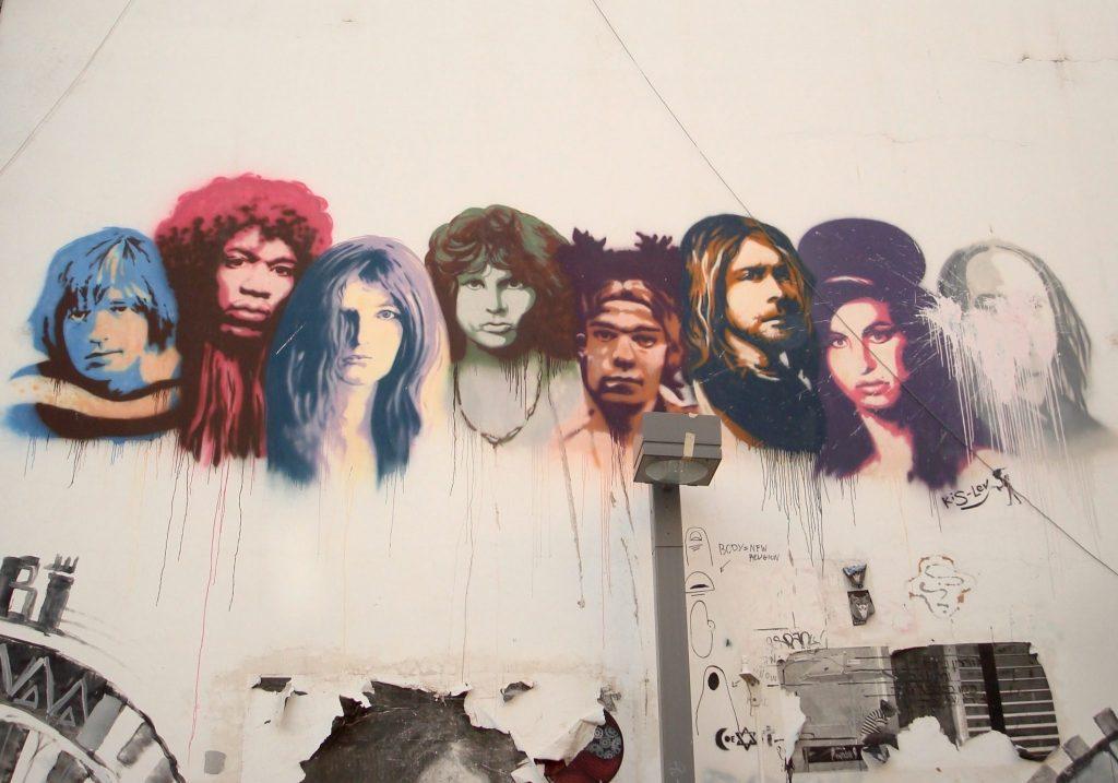 Acht Gesichter von Stars sind an die Wand gemalt