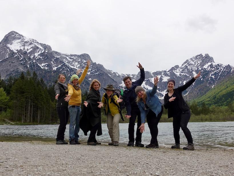 Sieben Personen am Ufer eines Sees mit Bergpanorama