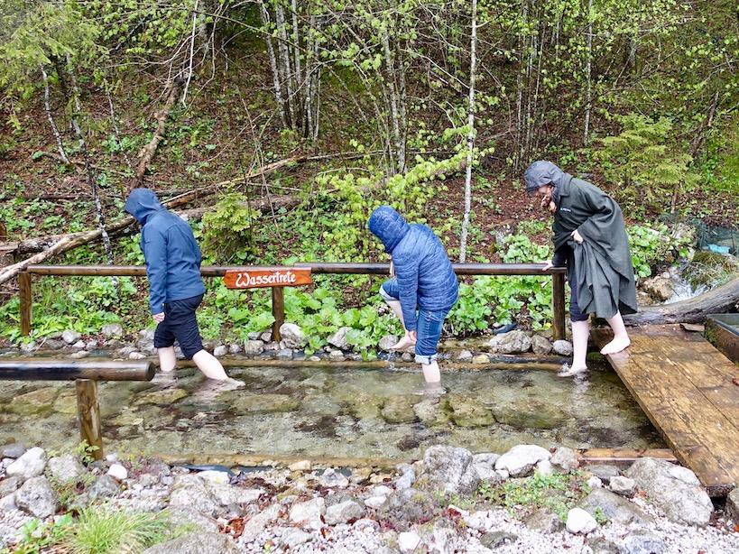 Drei Menschen gehen durch ein Wasserbecken